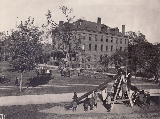 Children playing on a playground with slide, with Perkins Institution for the Blind in background.