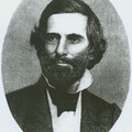 Howe with dark suit, white shirt with high collar, beard and mustache