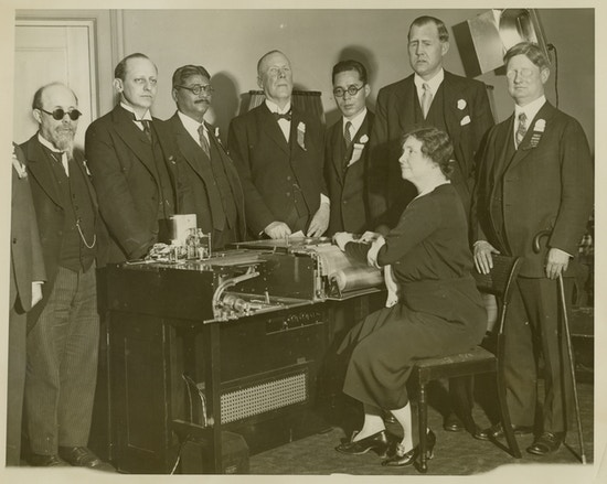 Keller sitting with hands on Visagraph, braille machine, men in suits stand around machine, Robert Irwin far right